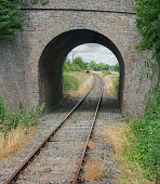 Single railway track going through a tunnel in rural England