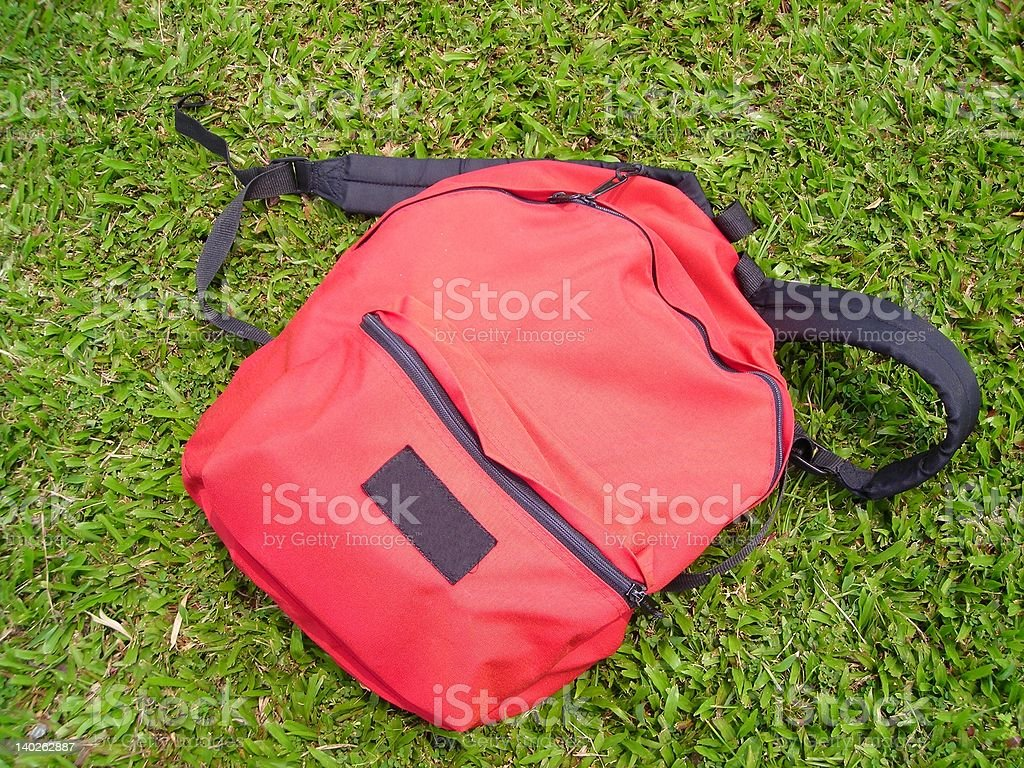 Single red bag against grass field stock photo
