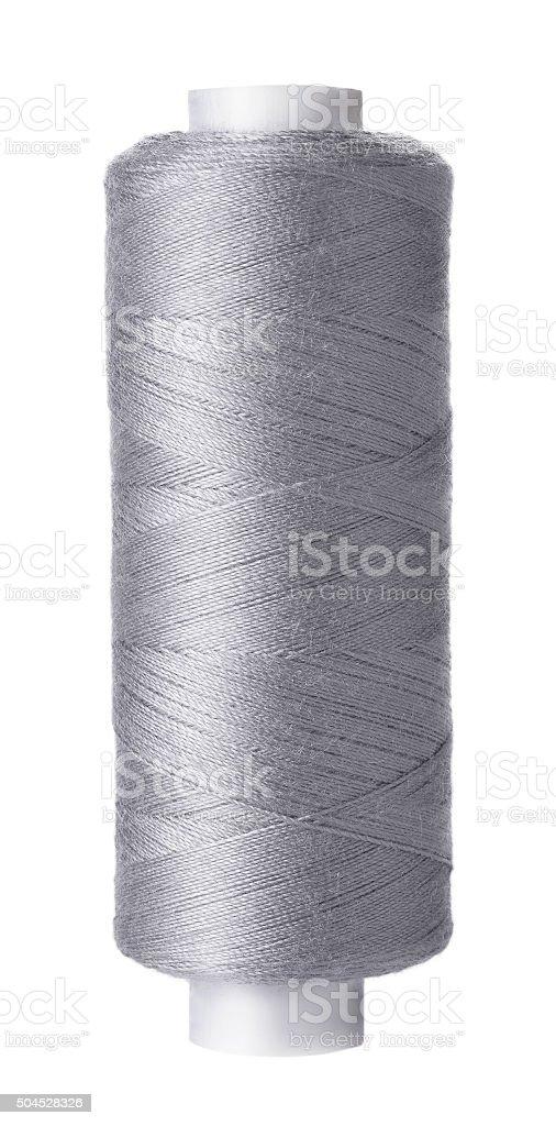 Single reel of gray thread on white background stock photo