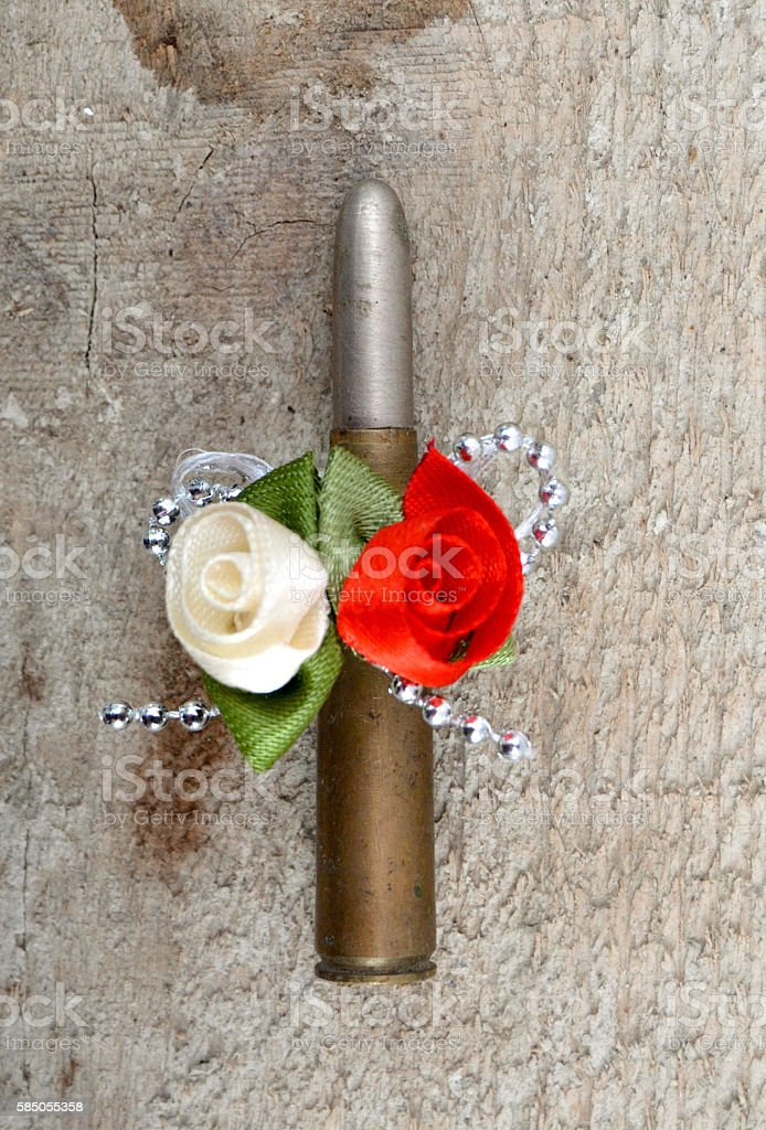 Single rifle bullet decorated with artificial flowers and ribbon stock photo