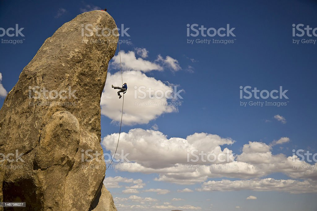 Single rock climber rappelling against giant rock formation royalty-free stock photo
