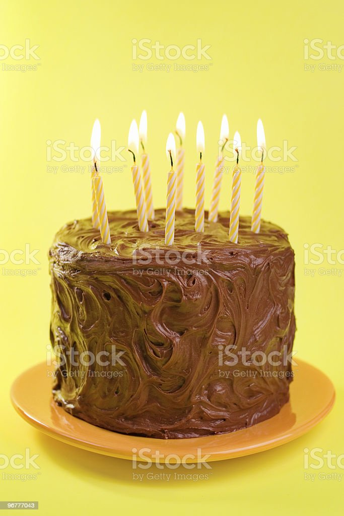 Single round chocolate cake with several candles on top stock photo
