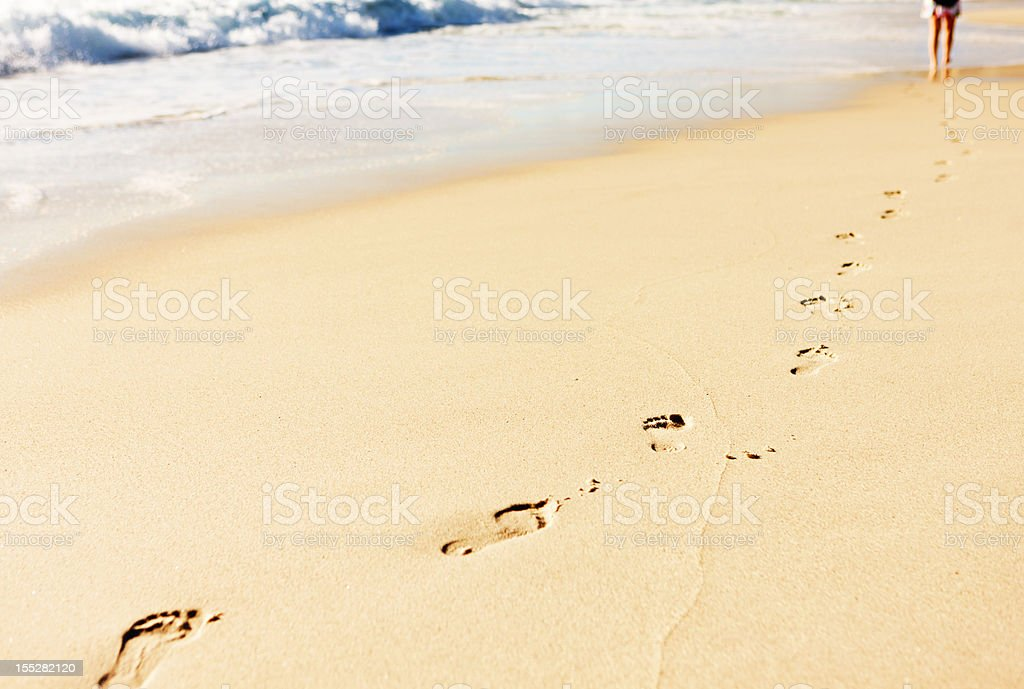 Single row of footprints on beach leading to distant person royalty-free stock photo