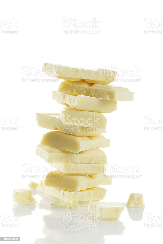 A single row of white chocolates creatively stacked up  stock photo