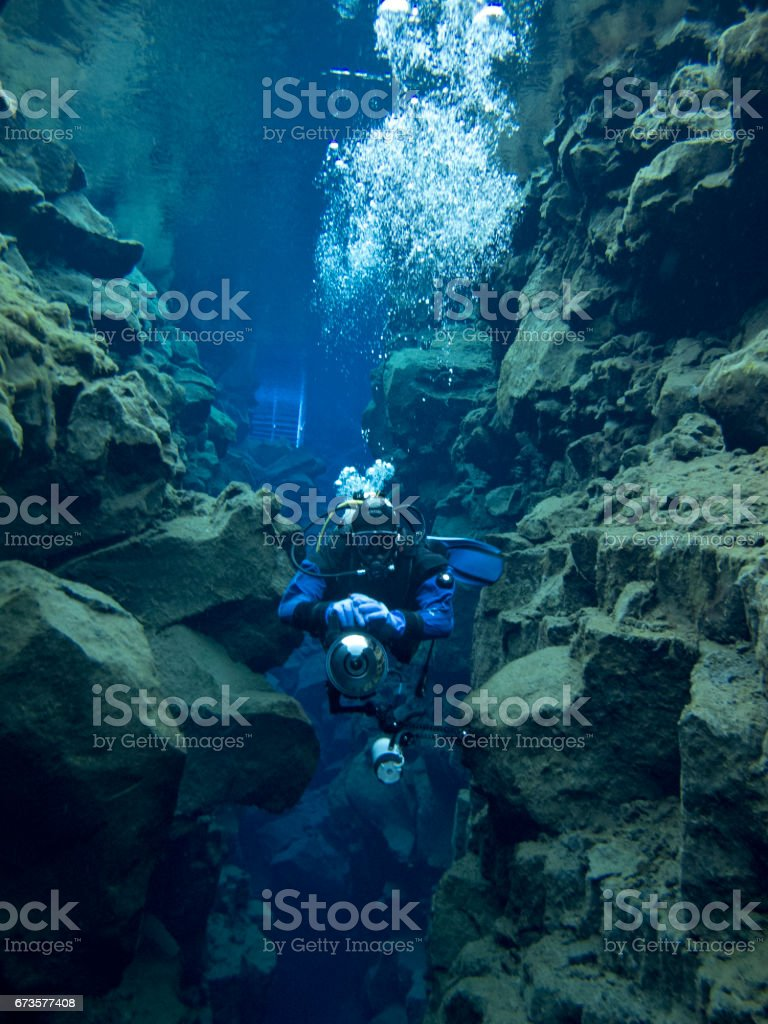 Single Scuba Diver in Narrow Rocky Slit at Continental Split at Silfra in Deep Section at Pingvellir National Park stock photo