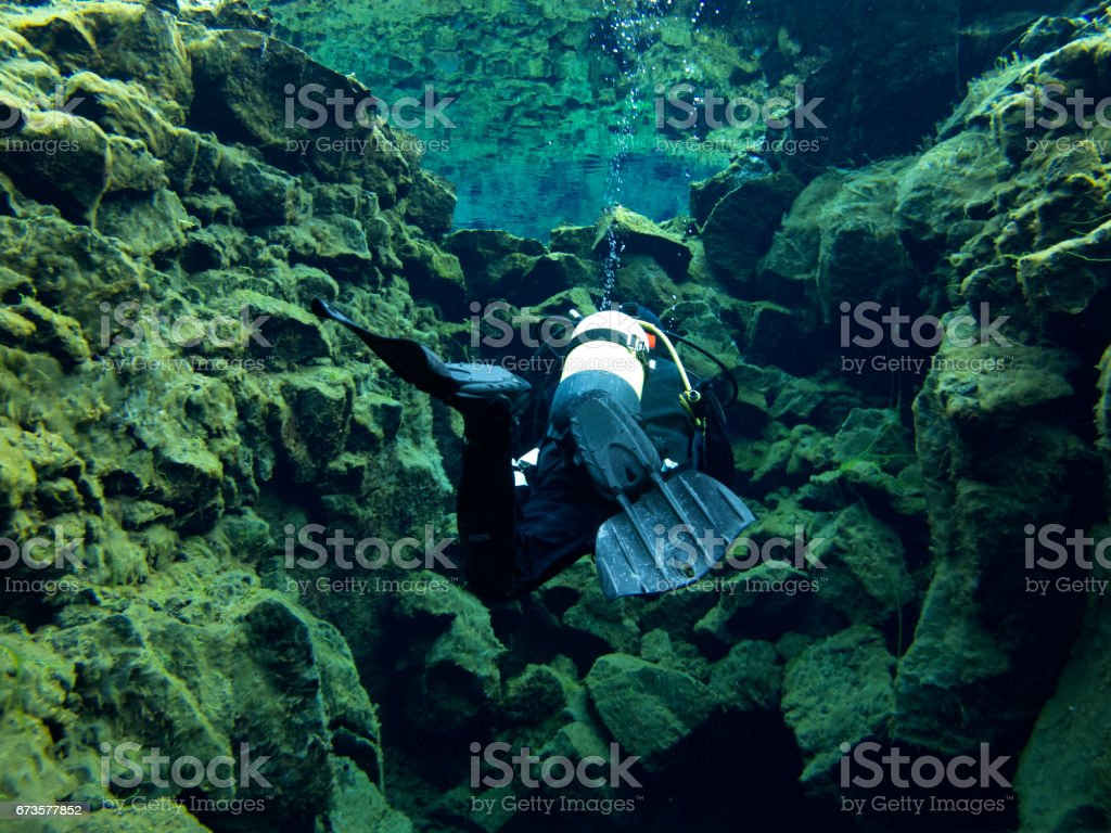 Single Scuba Diver Over Shallow Section View of Fins in Continental Split at Silfra in Deep Section at Pingvellir National Park stock photo