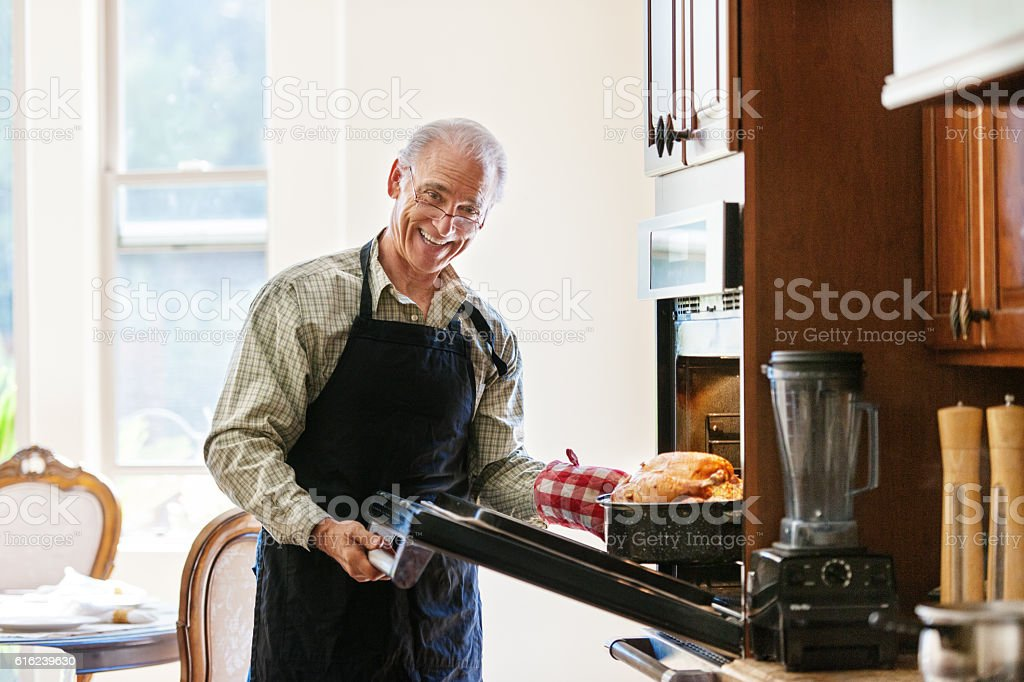 Single senior man cooking turkey stock photo