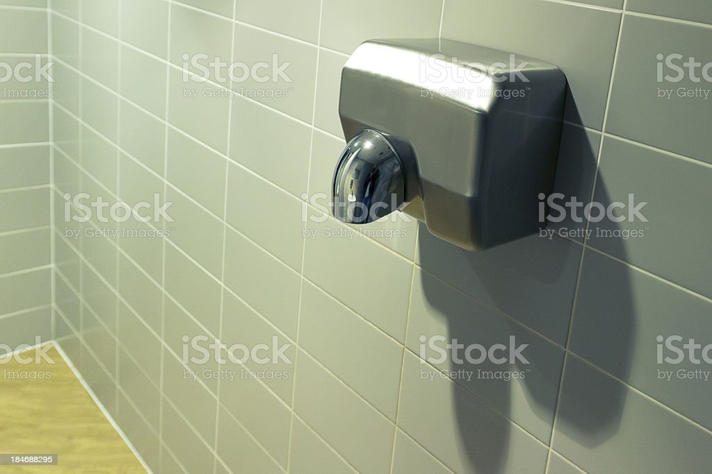 A single silver hand dryer in a bathroom stock photo