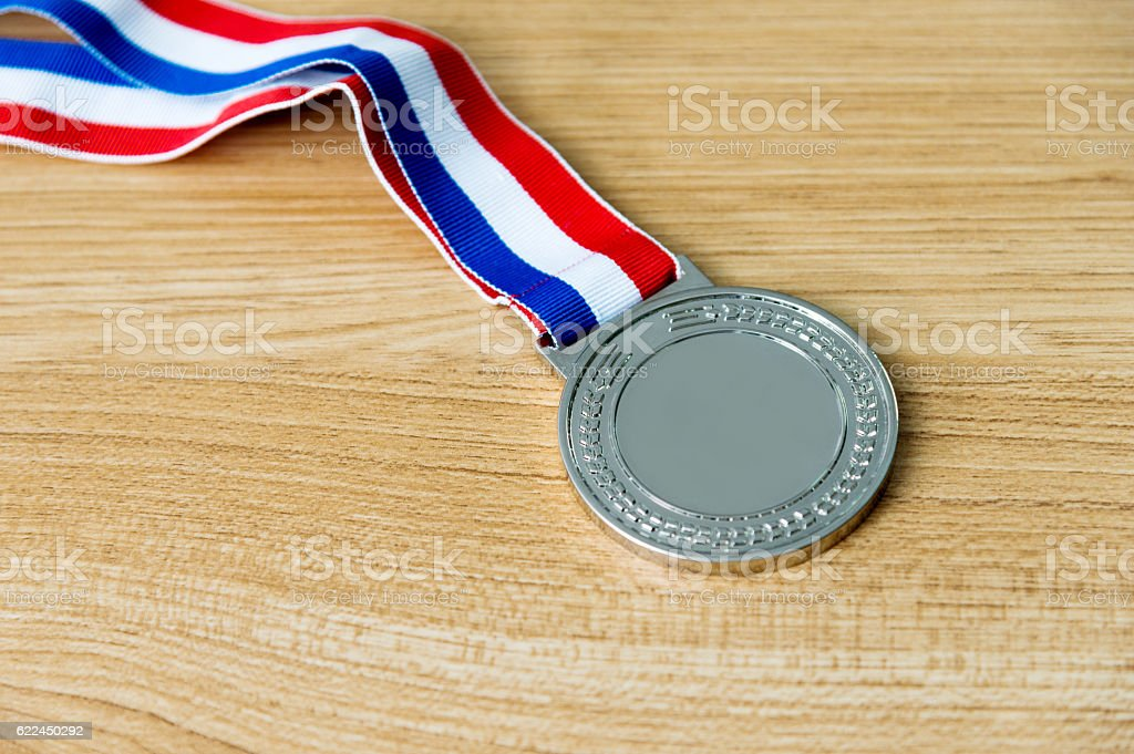 Single silver medal on wood desk stock photo