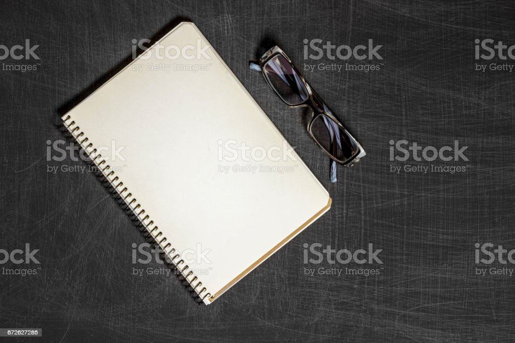 Single simple empty white notebook with a blank for drawing or writing and eyeglasses are on a Desktop from black chalkboard. Top view. Mockup. Flat lay stock photo