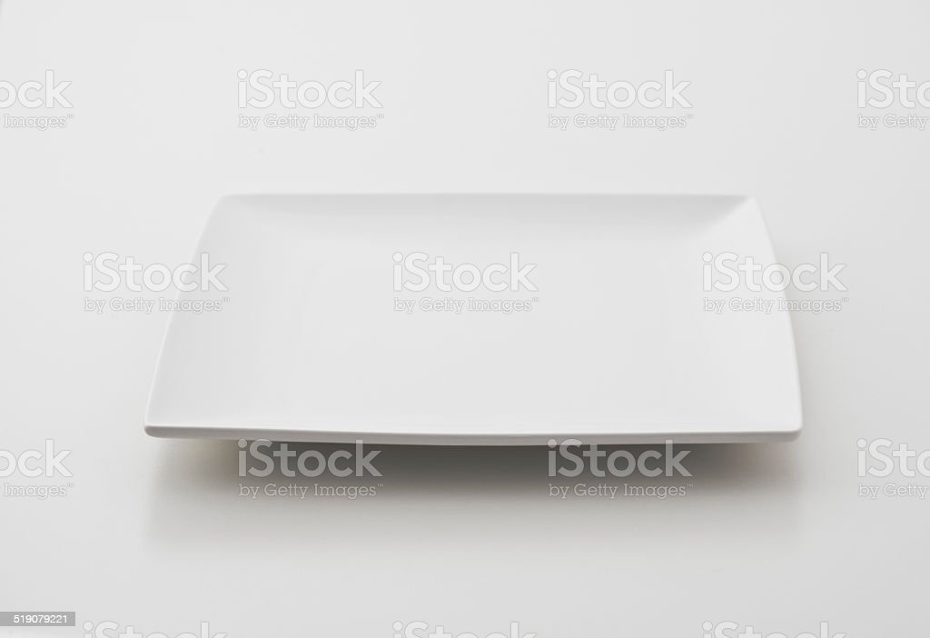Single square porcelain plate on white background stock photo