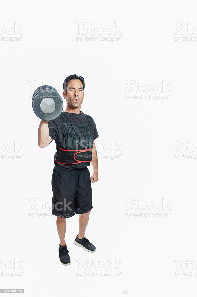 Single standing dumbbell press in weighted vest stock photo