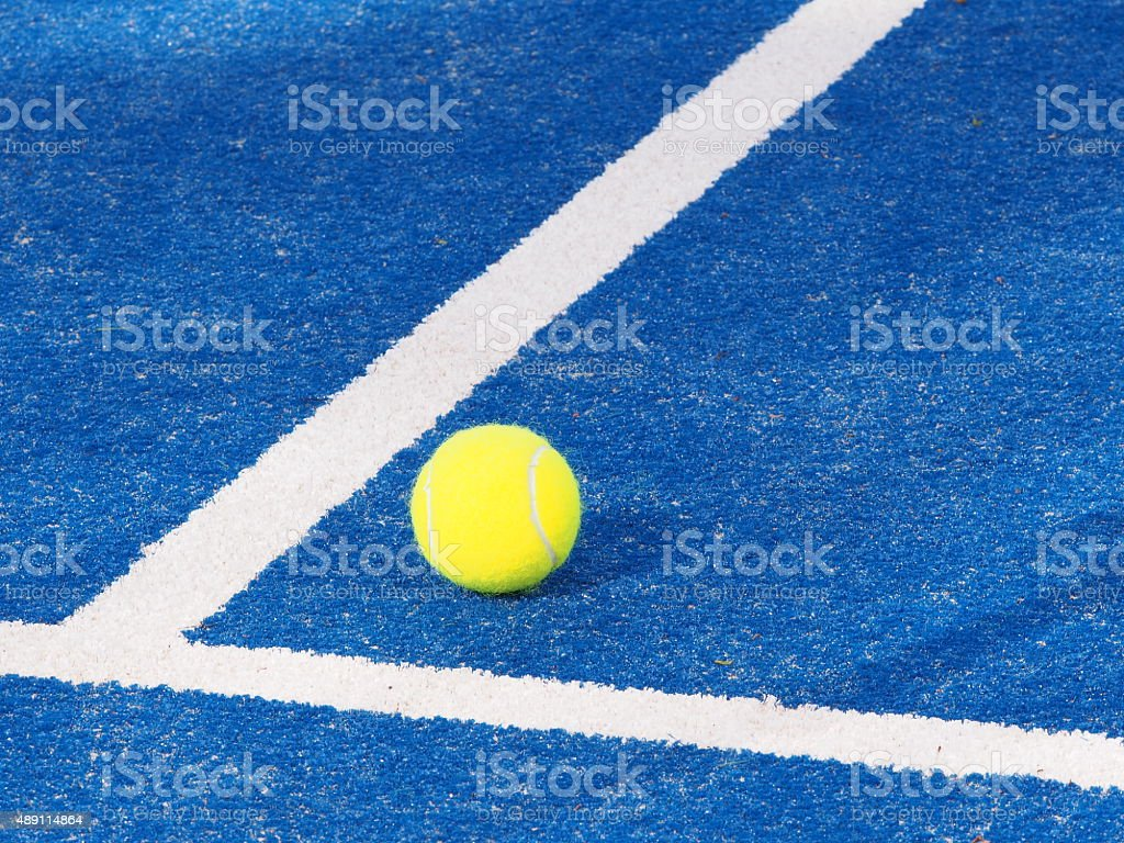 Single Tennis ball blue artificial grass court with lines stock photo