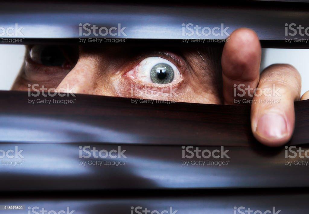 Single terrified eye peeps through Venetian blind,  staring in panic stock photo