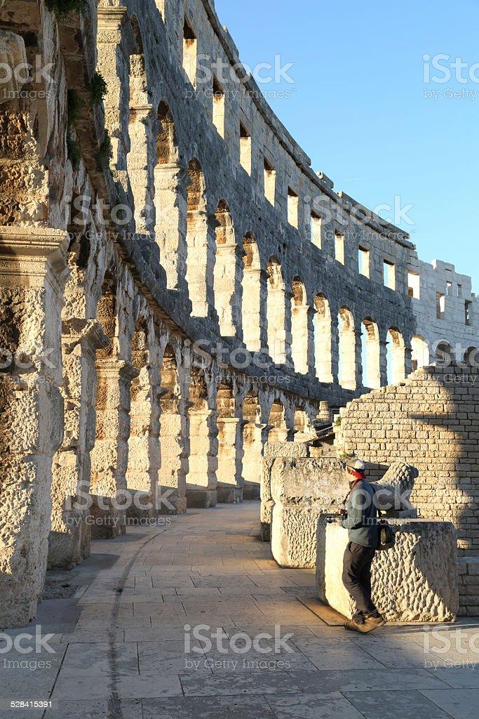 Single traveller explores coliseum structure, Pula Arena stock photo