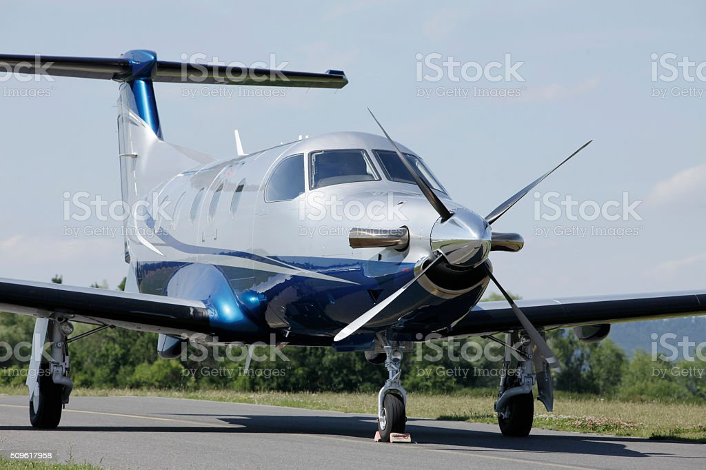 Single turboprop aircraft parked on runway. stock photo