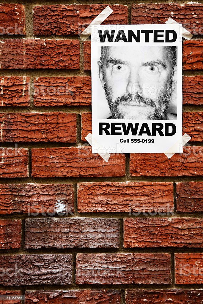 Single Wanted poster of desperate looking man on brick wall royalty-free stock photo
