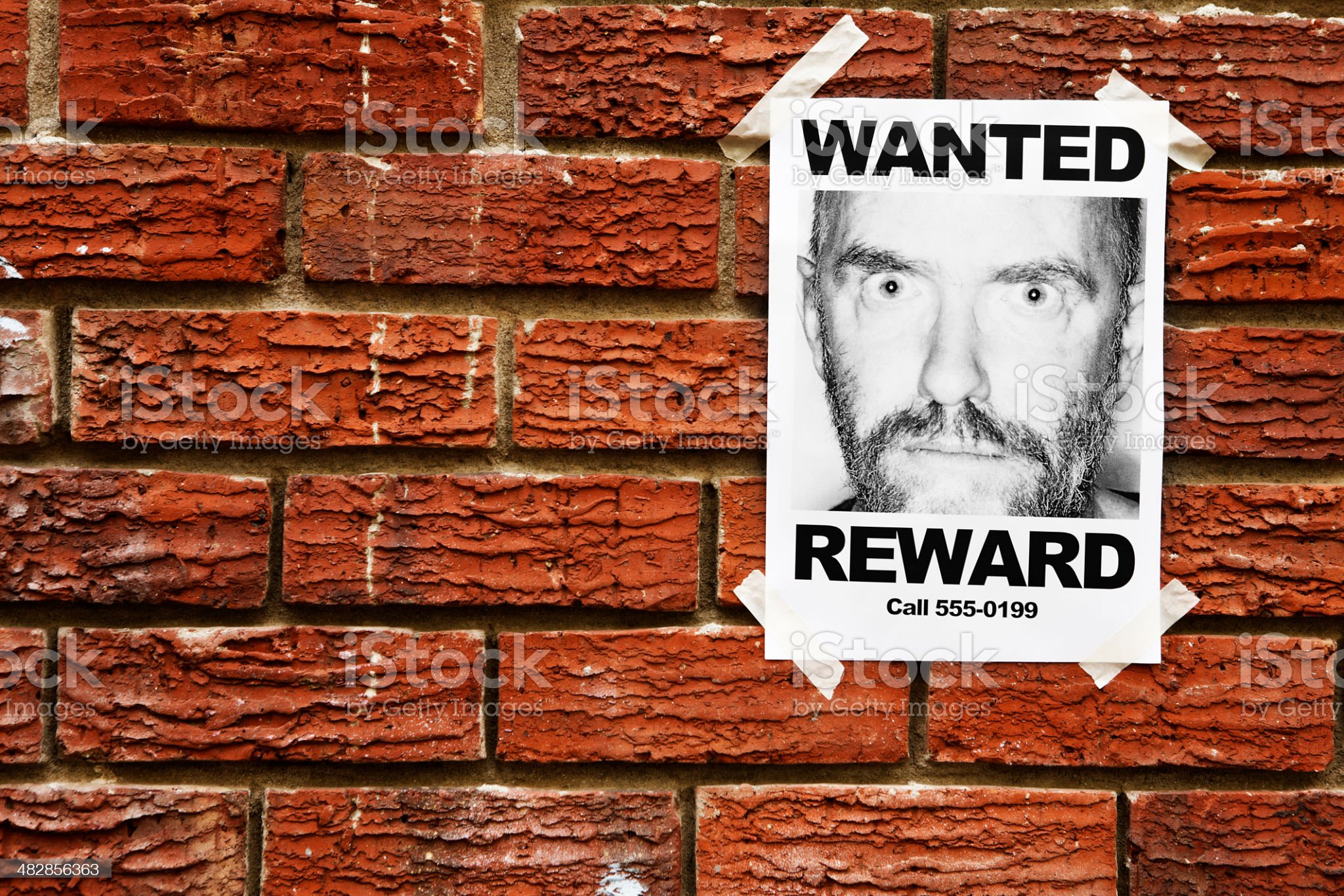 Single Wanted poster of wild eyed man on brick wall royalty-free stock photo