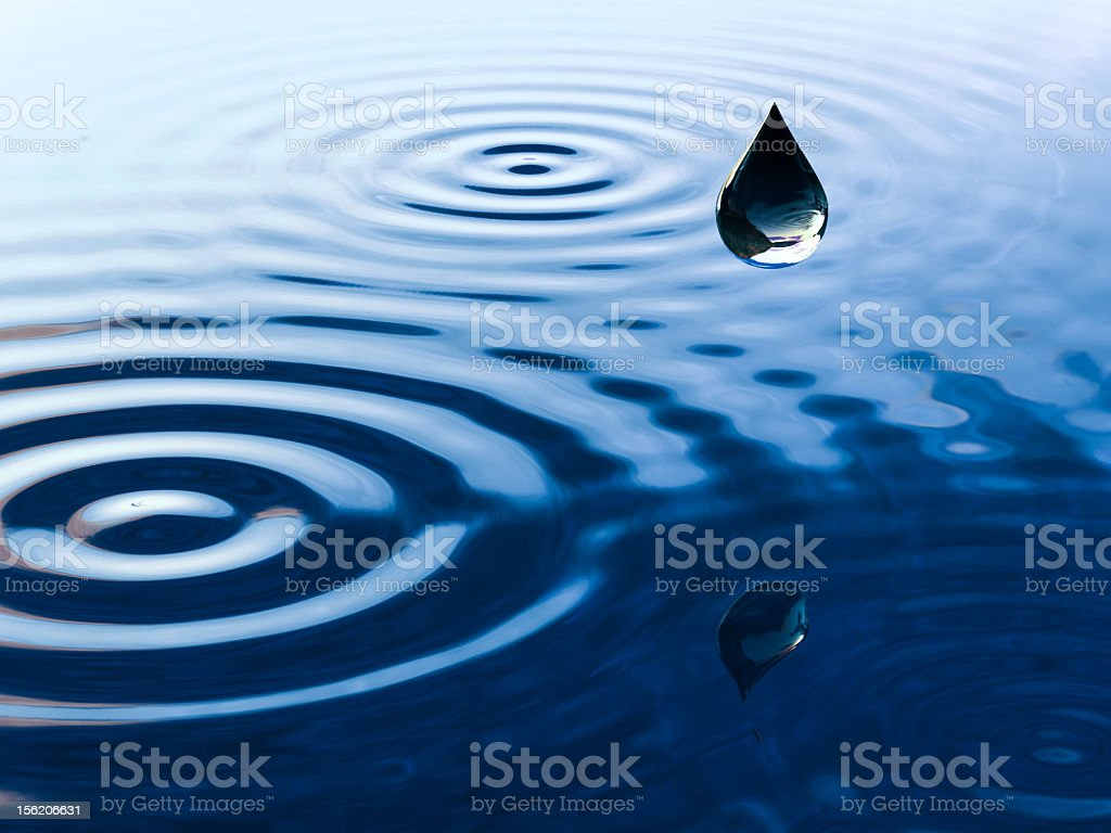Single water droplet captured hovering over water stock photo