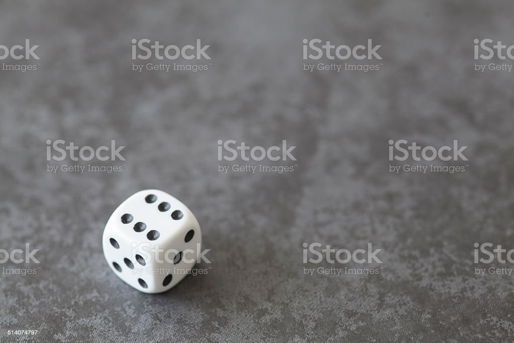 single white dice on grey background stock photo