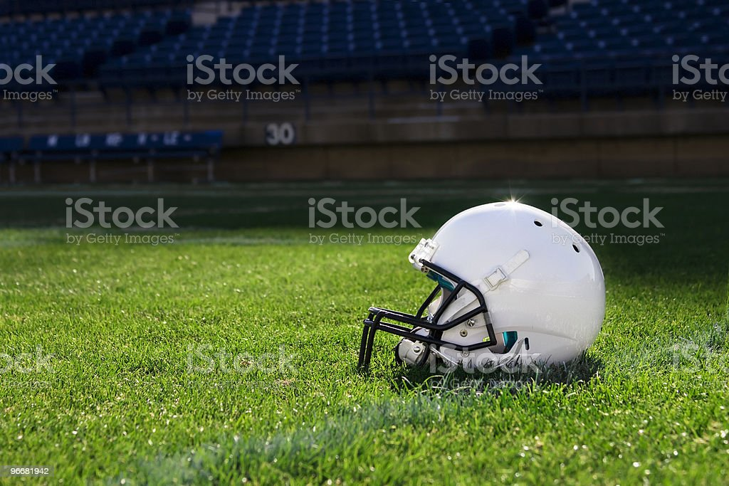 Single white football helmet on the field stock photo