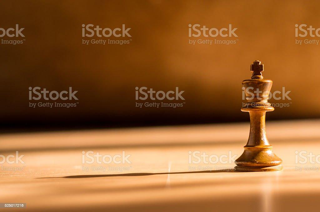 Single White King Chess Piece on Wood stock photo