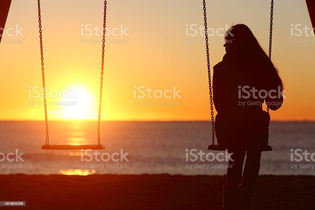 Single woman alone swinging on the beach stock photo