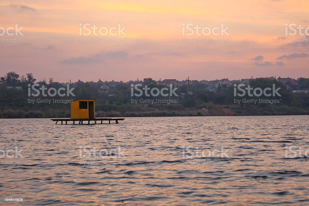 Single yellow wooden house stands in the middle of lake royalty-free stock photo
