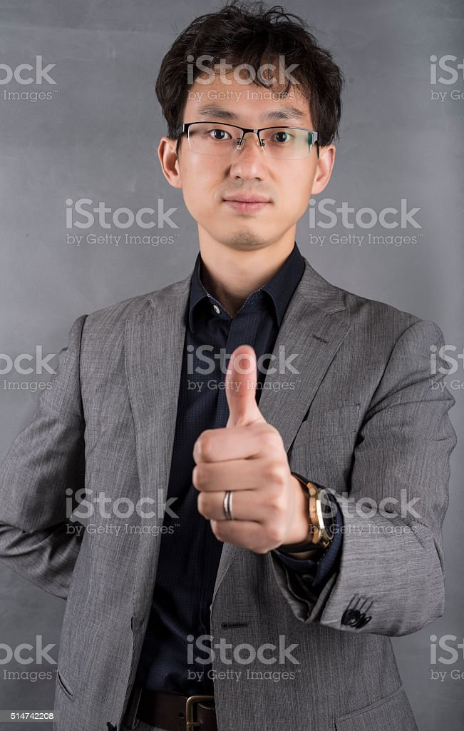 Single young asian businessman in front of a gray background stock photo