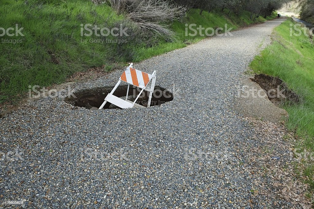 Sinkhole in Gravel Road stock photo