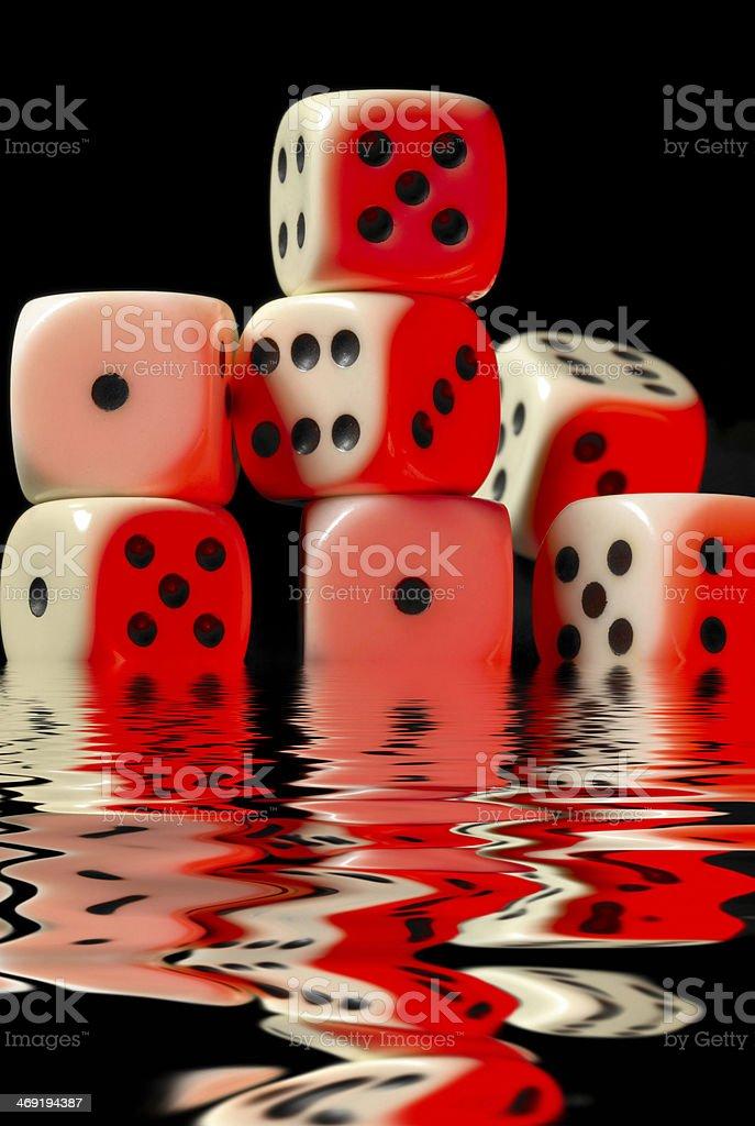 sinking pile of red illuminated white dice stock photo