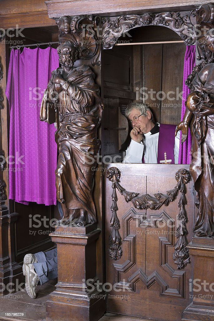 Sinner and priest in confession booth stock photo