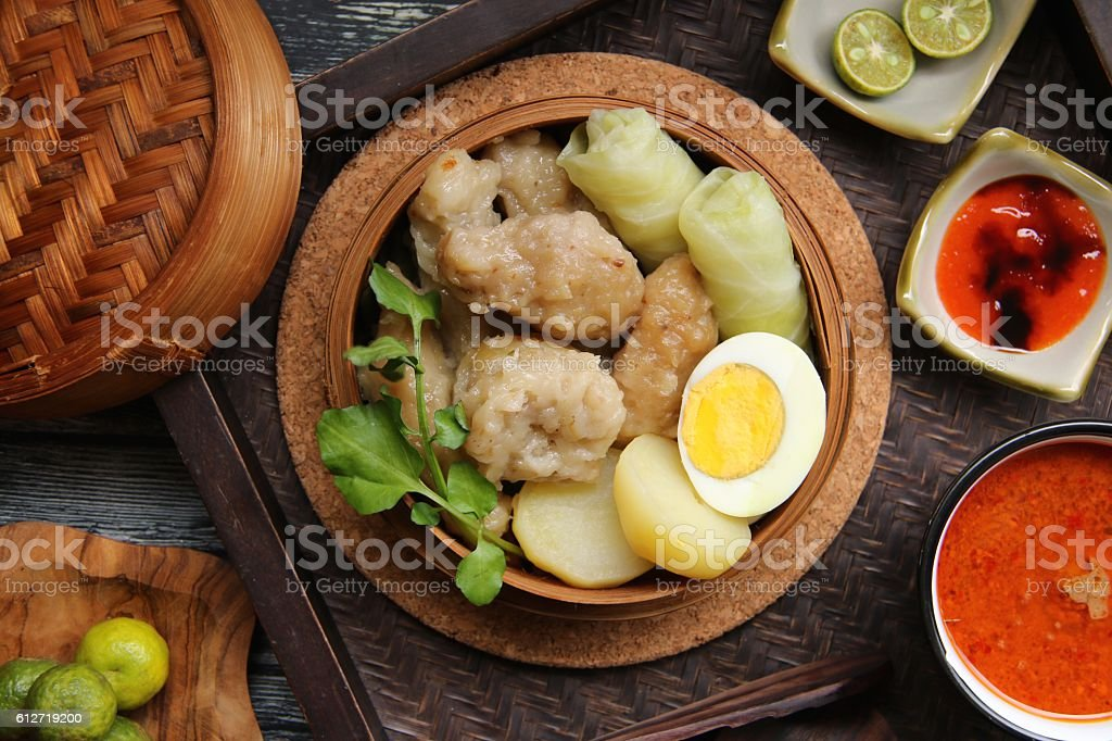 Siomay Bandung in Bamboo Steamer with Variety of Condiments stock photo