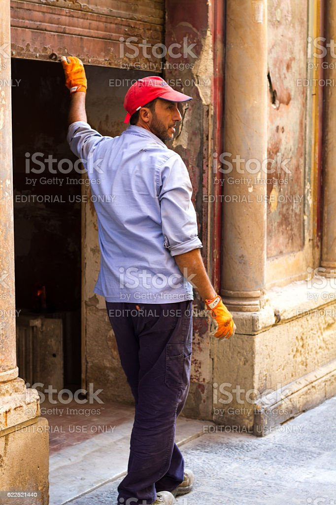 Siracusa, Sicily: Worker Pulling Down Roller Shutter on Storefront stock photo