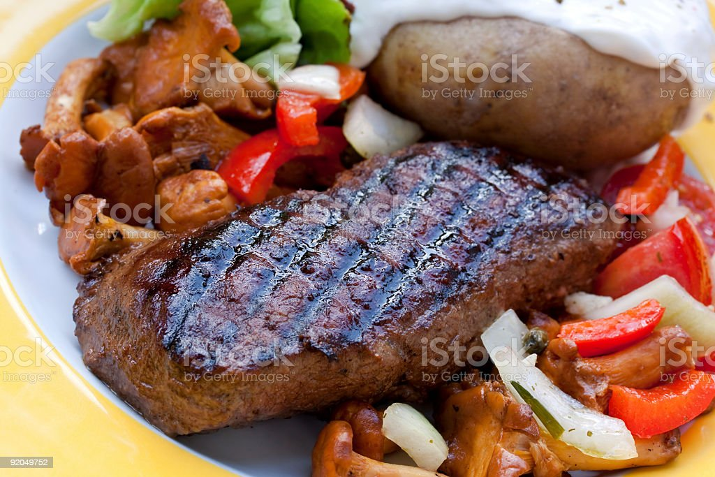 sirloin strip steak with baked potato and chanterelle royalty-free stock photo