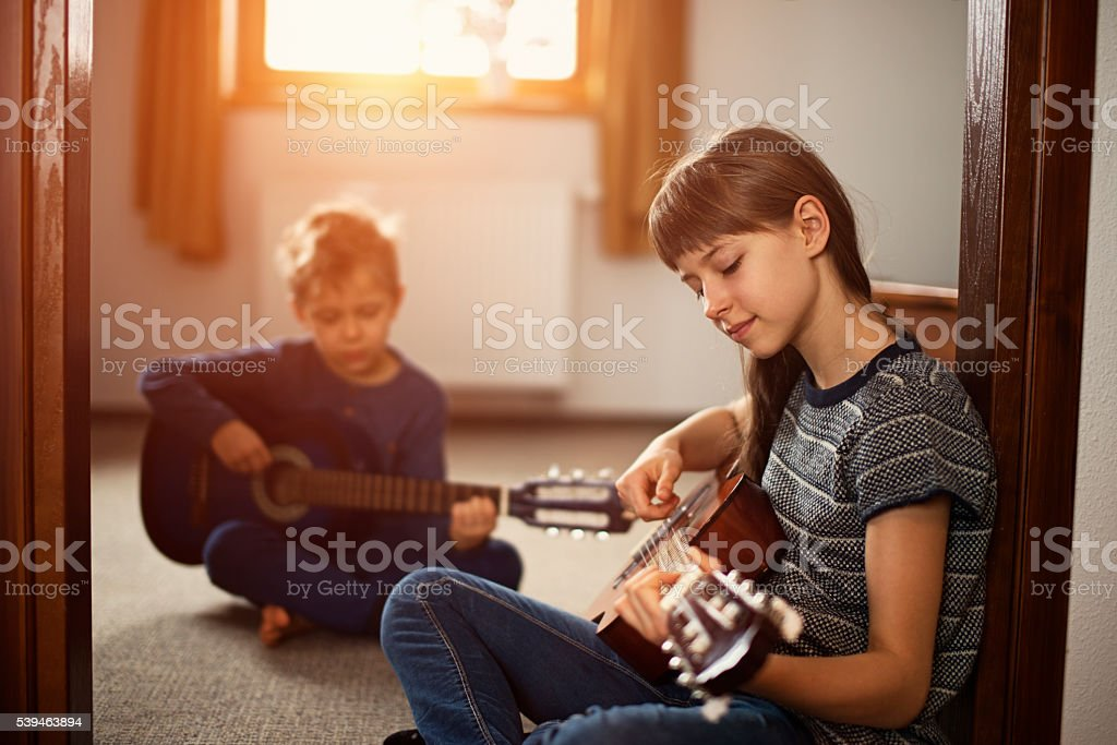 Sister and brother playing guitars together stock photo