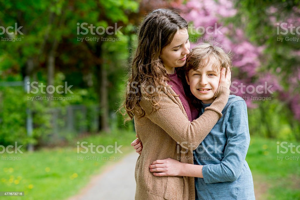 Sister Embracing Younger Brother stock photo