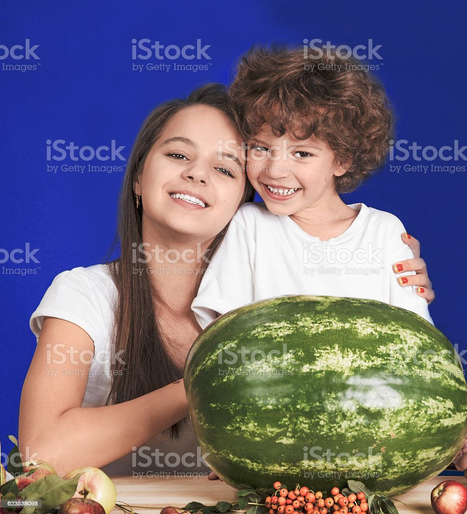 Sister hugging her brother sitting at the table. Blue background stock photo
