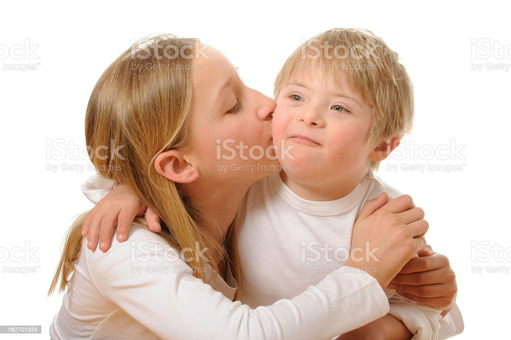 Sister kisses her brother with down syndrome royalty-free stock photo