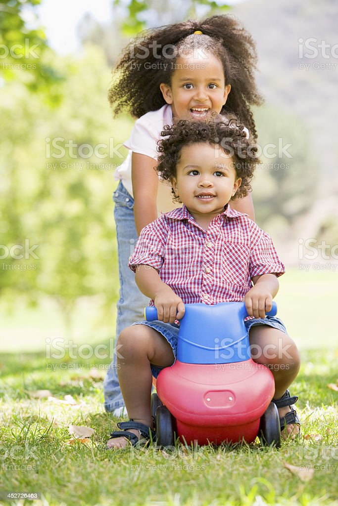 Sister pushing brother on toy with wheels smiling stock photo