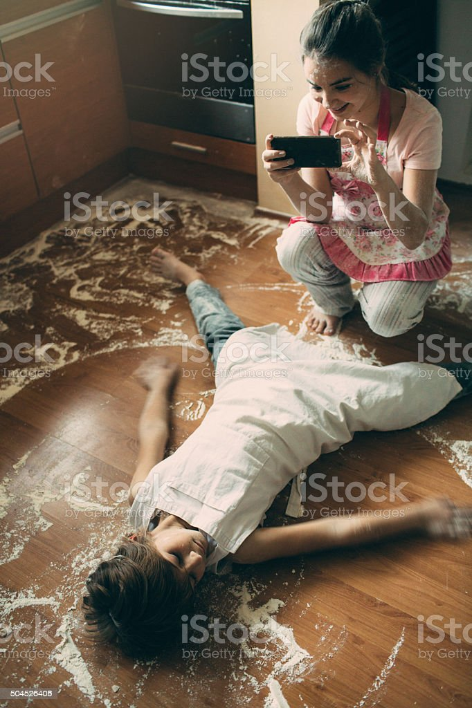 Sister taking photo of her brother lying on floor stock photo
