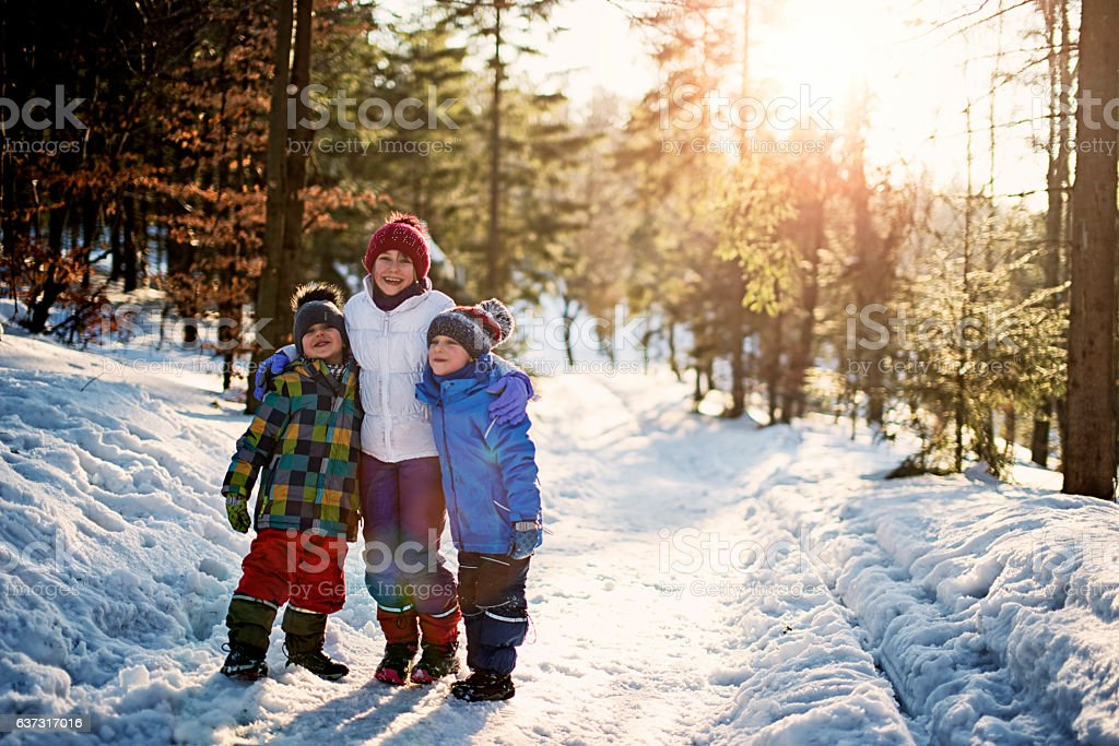 Sister with little brothers playing in winter forest stock photo