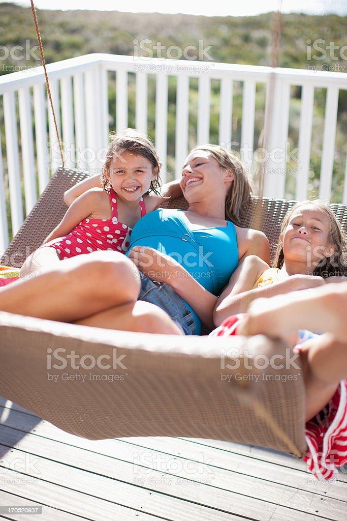sisters and mother relaxing on lounge chair on deck royalty-free stock photo