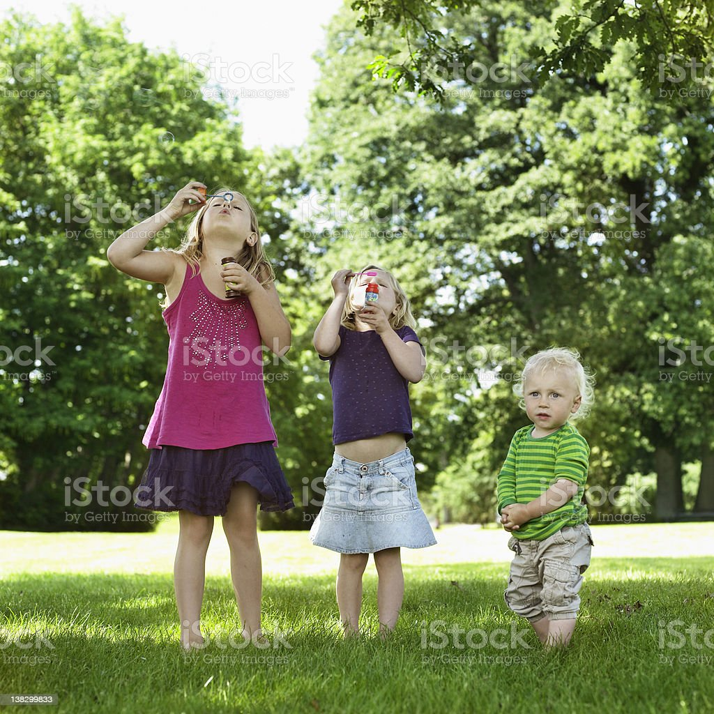Sisters blowing bubbles with brother stock photo
