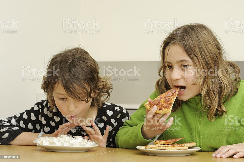 Sisters eating sweets and pizza stock photo