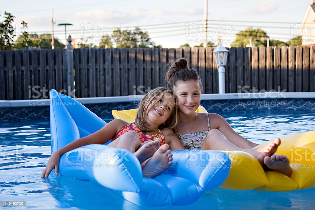 Sisters floating in the pool royalty-free stock photo