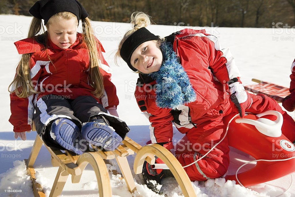 Sisters in snow on toboggan royalty-free stock photo