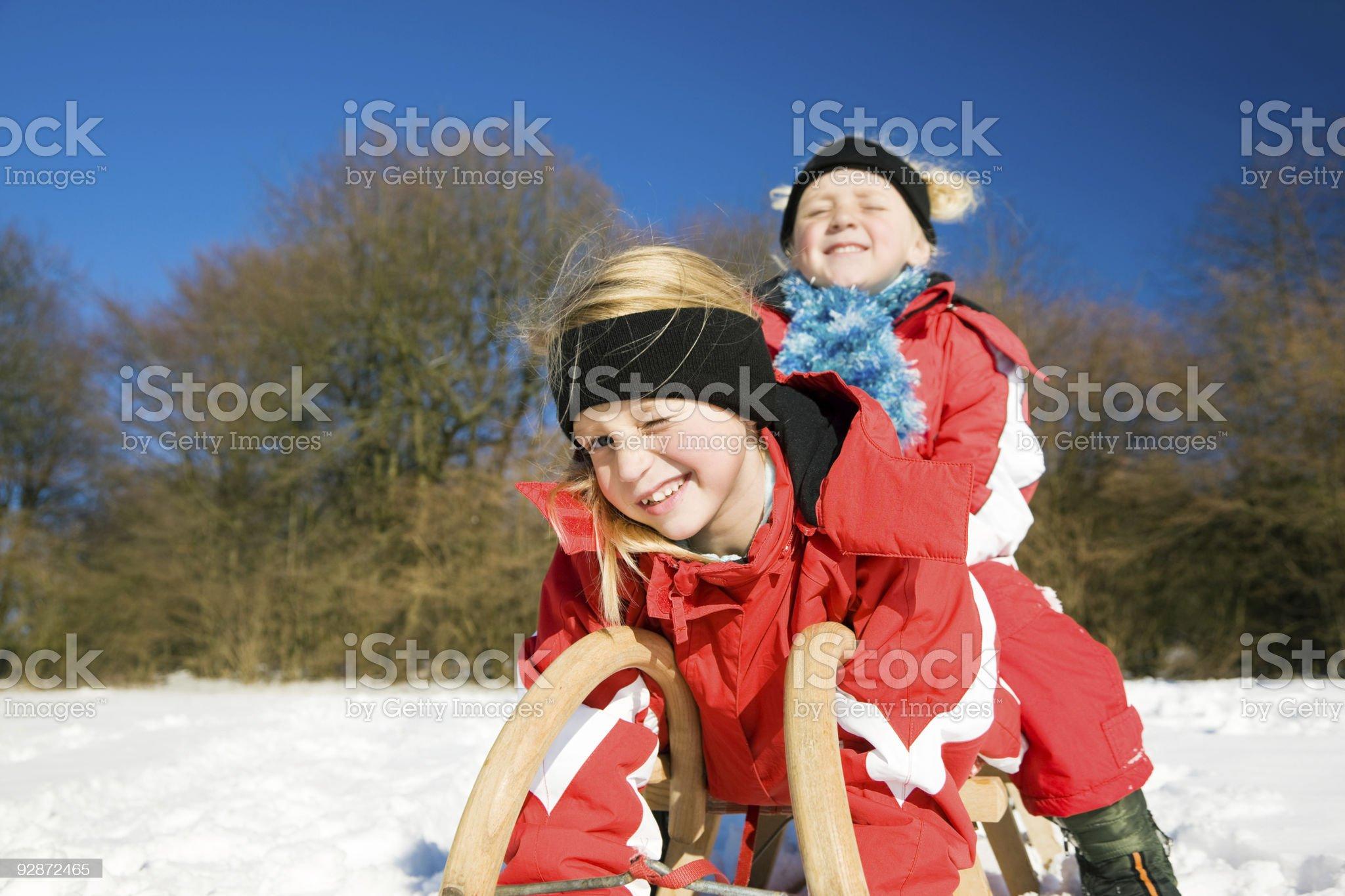 Sisters in snow on toboggan royalty-free stock photo
