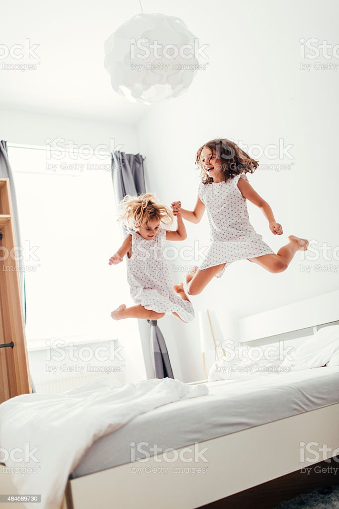 Sisters Jumping On The Bed. stock photo