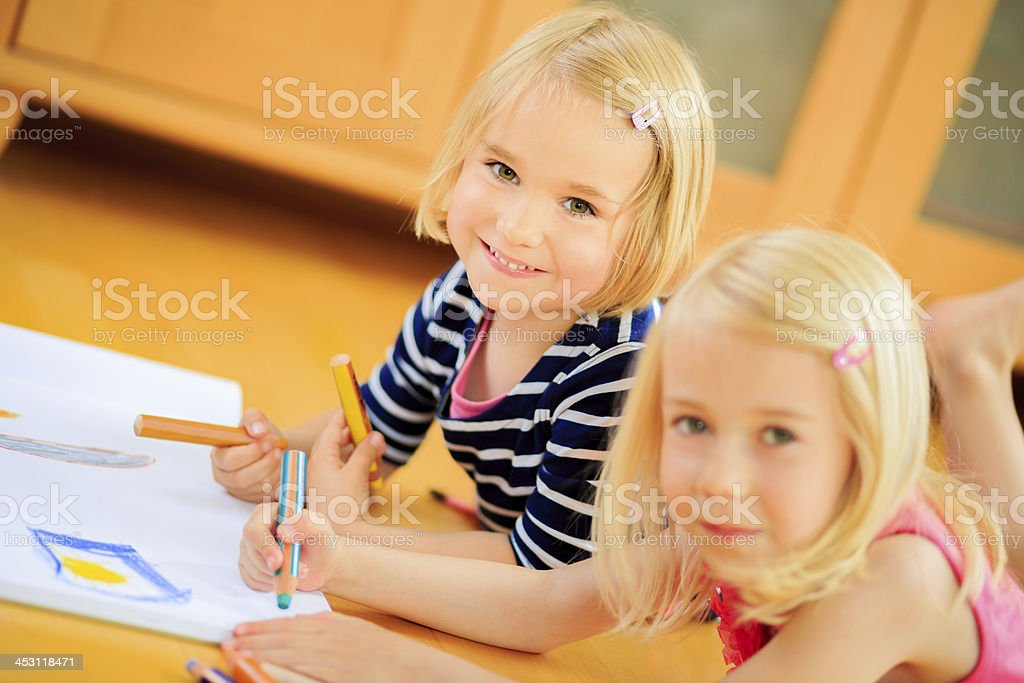 Sisters looking at camera while painting in living room royalty-free stock photo